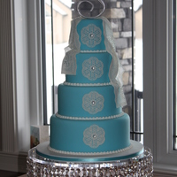 Blue With Lace Wedding Cake 4 tier wedding cake covered in blue fondant. Edible lace is used to finish this wedding cake.