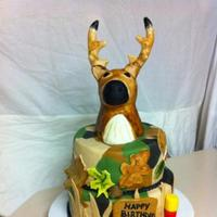 Deer Head/ Camo Fondant vanilla & red velvet cake covered in camo fondant. Deer is rct covered in fondant and hand painted. Hand painted fondant accents.