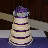 First Wedding Cake Round 4 tier covered in buttercream icing, Purple ribbon accents and sild flowers on top.