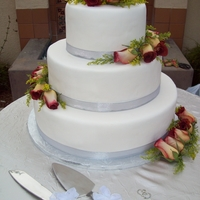 Wedding Cake With Fresh Flowers Chocolate cake moistened with hazelnut syrup, frosted with italian butter cream and covered with fondant. Decorated with fresh flowers and...