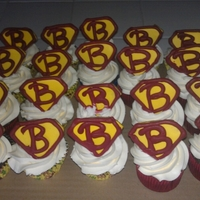 Superbill Cup Cakes Chocolate cupcakes with banana cream frosting. Decorated with sugar cookies to look like Superman logo with royal icing