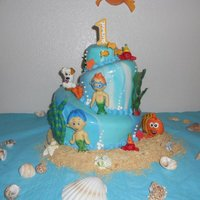 "Bubble Guppies My first topsy-turvey cake. Small cake was my grandson's ""smash"" cake. Couldn't get the eyes right on the modeling..."
