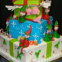 Elves   3 tier, silly elves into everything. Cake is all buttercream iced. Fondant elves and bows.