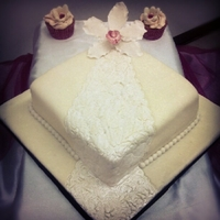 Single Tier Wedding Cake Single tier embossed wedding cake topped with a sugar cymbidium orchid with 100 cuppies topped with sugar orchids. Flavor~Marble w/Vanilla...