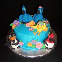 "Rio Cake Chocolate cake iced in buttercream with fondant flowers and leaves and fondant sculpted birds from the movie, ""Rio."""