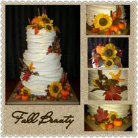 Fall Beauty *3 tier fondant wrapped with gumpaste flowers and leaves, fondant pumpkins and caramel/tootsie roll acorns.
