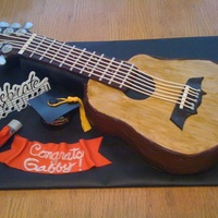 Guitar Grad I used the Wilton guitar pan but made a longer neck out of cardboard. Chocolate ganache covered the neck and sides, fondant on top for wood...