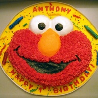 Elmo Face Wilton pan Elmo cake, butter cream icing, cake board covered with fondant yellow with colorful confetti sprinkles and fondant crayons.