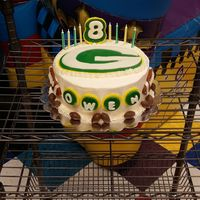 Greenbay Packers Football Cake   WASC cake dyed green and gold...vanilla BC. Fondant decorations and little chocolate candy footballs for boarder
