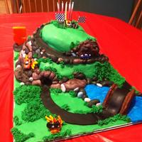 Race Car And Track Themed Chocolate cake with chocolate BC. Working tunnel through cake for cars to drive through. Fondant decorations. Used real toy mini cars for...
