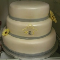 Sunflower Wedding Cake This Is A Vanilla Cake With A Pineapple Filling And Buttercream Covered In Mmf With A Gray Border And Yellow And Gr... Sunflower Wedding Cake. This is a vanilla cake with a pineapple filling and buttercream covered in MMF. With a gray border and yellow and...