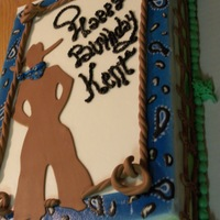 Western Cake The sides of the cake have hills and sky with clouds. Buttercream icing. Fondant cowboy, rope and fence.