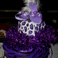 Purple Animal Print Cake Client's daughter was having a drag show for her sweet 16 party. Both tiers are covered in purple fondant, but the flash makes the top...