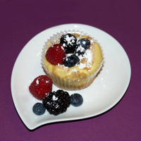 Vanilla Cheesecake Crunch-Top Cupcakes Vanilla cake topped with cheesecake and crumbs. Decorated with blueberries, blackberries and raspberries and dusted with powdered sugar.
