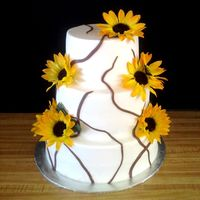 "Sunflowers Three tier White, Chocolate, and Strawberry cake with 6, 8 and 10 inch tiers. Covered with Buttercream icing. Fondant ""branches.&quot..."