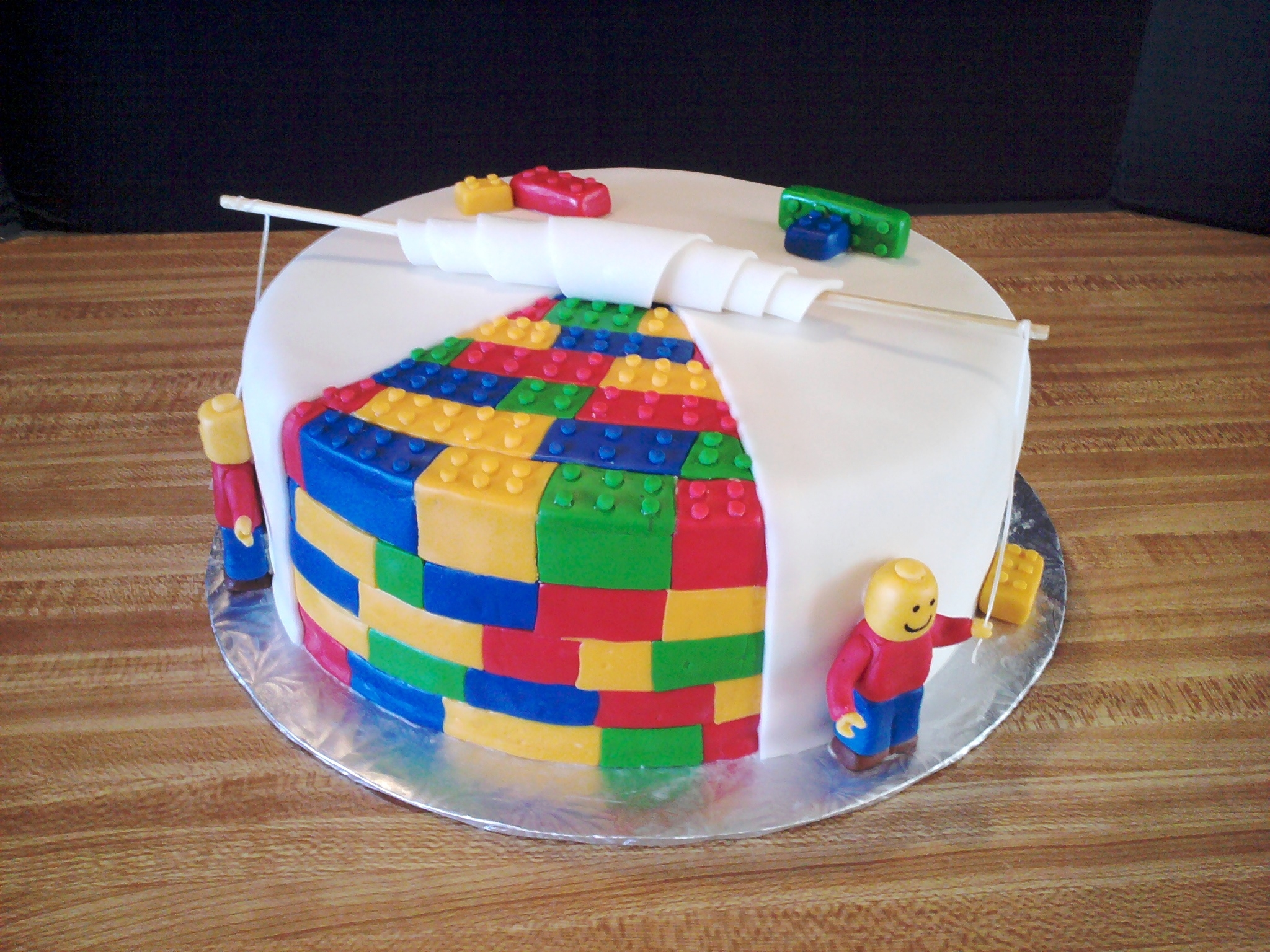 Lego Cake  10 inch Chocolate cake with Vanilla Icing, covered in fondant. Legos and Lego men made of fondant. Dental floss ropes and bamboo skewer...