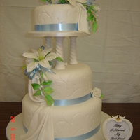 White Wedding Cake Traditional round 3 tiered wedding cake with hand-made lilies, roses, filler flowers and leaves. Sides embossed , textured draping , all...