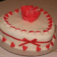 Sweetheart Cake Strawberry Buttercream Cake covered in fondant decorated with star shaped border covered with red fondant hearts and a fantasy flower in...
