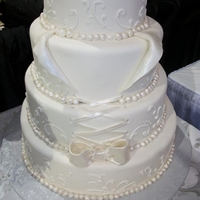 White Round Fondant Covered Wedding Cake Butter Almond wedding cake covered w/ fondant and decorated with buttercream scroll designs