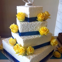 White, Blue And Yellow Wedding Cake White buttercream frosting, blue ribbon with yellow roses.