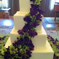 White - Purple Orchids Wedding Cake White buttercream frosting with fresh orchids.
