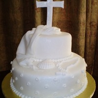 Baptism This cake was for a baptism. The cross, dove, sea shell and rosary were made of fondant.