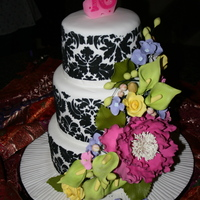 Sweet 16 Cake Damask design is stenciled using black RI on fondant. Gum paste flowers are roses, hydrangeas, calla lily and a peony, along with leaves...