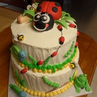 Critter's Cake 2 tier yellow buttercream filled with lemon curd. All accents including the critters are made of fondant.
