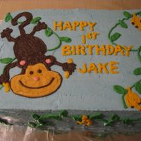 Monkey Cake 1/2 sheet cake frosted in buttercream. Monkey, vines and bananas in buttercream.