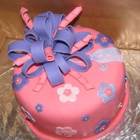 "Present Cake 8"" round cake with fondant. Pink and purple fondant flowers with shimmer dust. Fondant bow and squiggles."
