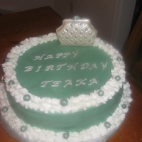 1351107449.jpg Buttercream with chocolate purse. Lettering and balls are fondant.