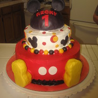 Mickey Mouse frosted in whipped cream and molding chocolate accents and the mickey mouse is cover in molding chocolate