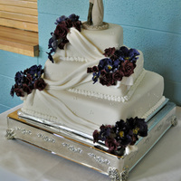 Orchids And Roses Wedding Cake Purple sugar orchids and burgundy sugar roses. White fondant and royal icing piped accents.
