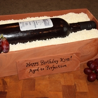 Wine Bottle Cake The wine bottle and the sides of the box are fondant. The wood chips were shaved white chocolate. The label on the wine bottle is edible...