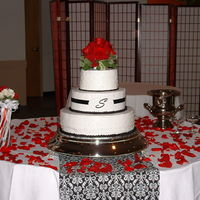 Black & White Wedding Cake W/splash Of Red White cake on bottom and top tier with raspberry filling. Middle tier has orange cream cheese filling. Fondant symbol in the middle with...