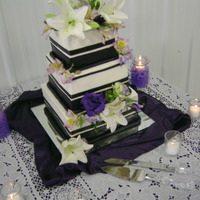 Square Cake In Plum With Lillies Covered in BC with plum fondant accents and flowers. Cake held up pretty well for a 96 degree day with high humidity, in a pole shed. I was...