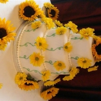Sunflower Wedding Cake With Yellow Daisies 6, 9, and 12 rounds with white fondant and real sunflower and daisies. The bride got the idea online, I don't know who the artist was...