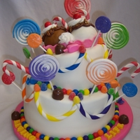 Livin' The Sweet Life Topsy-Turvy cake covered in marshmallow fondant. Decorated with fondant gum drops, royal icing swirled lollipops, gum paste candy canes,...