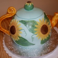 Sunflower Teapot Cake Fondant covered, including sunflowers. Hand painted leaves. Gumpaste handle and spout (hand modeled, also painted to look woodish/antiquey...