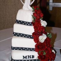 Square Black And White Fondant covered cakes with fondant polka dots and ribbons, royal icing monogram. Silk flowers.