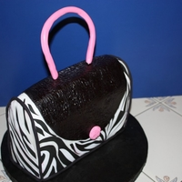 Zebra Purse Pink Handle Three layer pound cake covered in fondant. Handle is gumpaste.