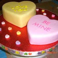 Conversation Hearts Fondant covered hearts decorated as conversation hearts on a round board with conversation heart candies decorating the board with a...