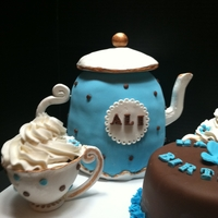 Tea Party Tea pot made out of 6 inch rounds and 6 inch wonder mold panTea cups made out of gumapaste and then filled with a cupcake
