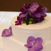 Round/square Wedding Cake With Fresh Vanda Orchids Cake is chocolate mud filled with ganache and covered in fondant. Fresh flowers were added at the reception - shame they displayed the cake...