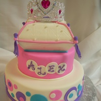 Princess Alex   3 tiered cake covered in fondant and accented with pearls, buttercream and glitter.