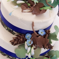 True Blue Camo!   Camo themed wedding cake finished with IBC and accented with acorns, pine cones, oak leaves and blue ribbon.