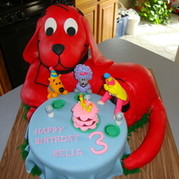 Clifford The Big Red Dog CLIFFORD IS CARVED FROM RKT, COVERED IN WHITE CHOCOLATE THEN RED CHOCOLATE FONDANT, ALL EDIBLE EXCEPT STRUCTURAL ITEMS, CAKE IS THE TABLE...
