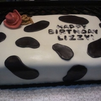 Cowprint Birthday Cake Chocolate fudge cake with chocolate mousse filling and buttercream icing. Covered in MMF. All decorations handmade MMF.