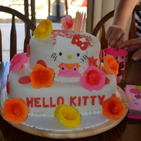 Hello Kitty Two tier Hello Kitty Cake, in white, pink, orange and yellow, with flower accents