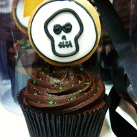 Skull Cupcakes   chcolate ganache cupcake. Topping is dark chocolate ganache and a skull lollipop on top!